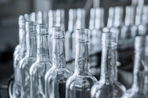 Glass bottles in production waiting for laser based defect inspection